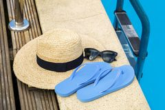 Straw hat with flip flops and sunglasses near swimming pool Stock Image