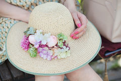 Straw hat with flowers in hands of young girl Royalty Free Stock Photo