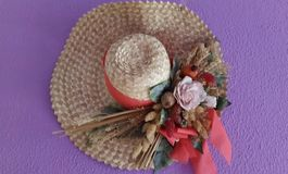 Straw hat with flowers. Hanging on a purple wall Stock Photos