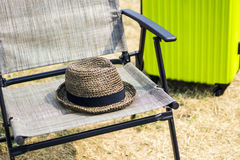 Straw hat on a folding chair and suitcase Royalty Free Stock Photography