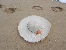 Straw hat and footprint on sandy beach sea Stock Photography