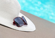 Straw hat, glasses by the pool Royalty Free Stock Photography