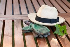 Straw hat and gloves on a garden table concept peace, finished work, gardening stock image