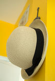 Straw hat hang on yellow wall Stock Photography
