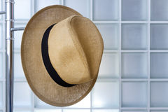 Straw hat hanging on a metal hanger. Stock Image