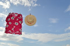 Straw hat and hawaii shirt  on clothesline Royalty Free Stock Photo