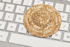 Straw hat on keyboard Stock Images