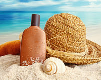 Straw hat with lotion on the beach Royalty Free Stock Photos