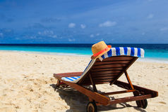 Straw hat on a lounge chair at sand beach Stock Image