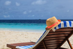 Straw hat on a lounge chair at tropical beach Royalty Free Stock Images