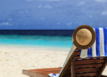 Straw hat on a lounge chair at tropical beach Stock Image