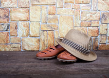Straw hat and moccasins on a wooden table in front of a stone wa Royalty Free Stock Photos