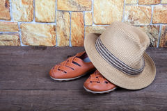 Straw hat and moccasins on a wooden table in front of a stone wa Royalty Free Stock Photo