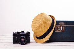 Free Straw Hat Old Suitcase And Camera On White Wooden Floor Near Wall Stock Photography - 102641402