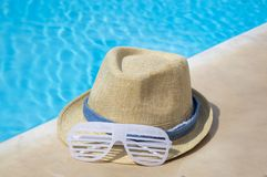 Straw hat and party sunglasses by the pool Royalty Free Stock Photography