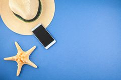 A straw hat, a phone and a starfish on a blue background. Top view Copyspace stock photo