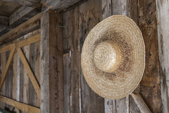 Straw hat. Picture of a straw hat hanged on the inside wall of a wooden barn Stock Image