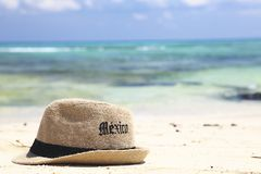 Vacation in mexico. Straw hat resting on Mexican beach Royalty Free Stock Image