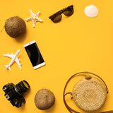Straw hat, retro film camera, bamboo bag, sunglasses, coconut, pineapple, sea shells and starfish, air plane, notebook. Summer traveler accessories flat lay royalty free stock images