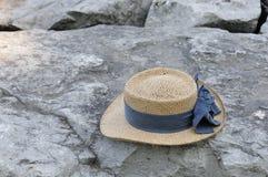 Straw hat on rocks Stock Photos