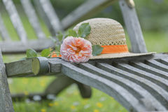 Straw hat and rose on a wooden recliner royalty free stock photography
