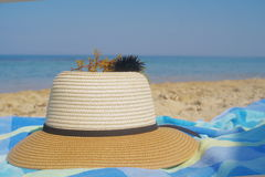 Straw hat and sea urchin on a towel and  sand near the shore on a beach in summer Royalty Free Stock Images