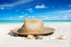 Straw Hat and Seashells on the Beach Stock Photos