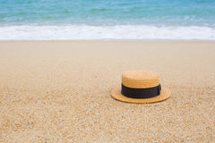 Straw hat on the shore of a beach Stock Image