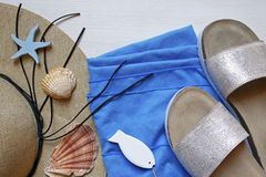 Straw hat, slippers, beach towel and seashells Royalty Free Stock Image