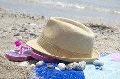 Straw hat slippers and a towel on the beach with sea in backgrou Royalty Free Stock Photos