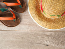 Straw hat and slippers on wooden table. Top view. Summer vacation planning concept stock photography