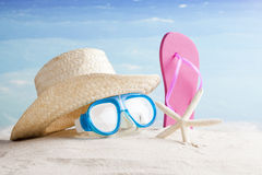 Straw hat, snorkel mask and flip flops on a tropical beach Royalty Free Stock Images