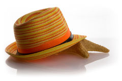 Straw hat and starfish. Starfish lying under a straw hat Stock Image