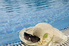 The straw hat and sun glasses. Lie on the brink of pool stock photo