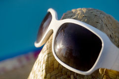 A straw hat with sun glasses sitting beside pool Royalty Free Stock Photography