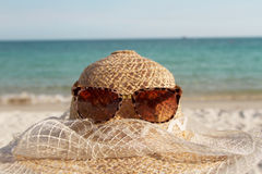 Straw hat and sun glasses on tropical beach Stock Photo