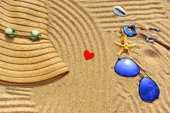 Straw hat, sun glasses and wood heart on a tropical beach Royalty Free Stock Images