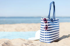 Straw hat, sunglasses and bag lying in the sand. Hats and summer concept - white straw hat, sunglasses and bag lying in the sand on the beach Stock Photography