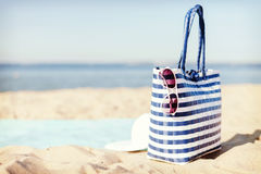 Straw hat, sunglasses and bag lying in the sand Royalty Free Stock Image