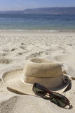 Straw hat and sunglasses on the beach Royalty Free Stock Images
