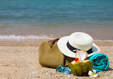 Straw hat, sunglasses, beach towel with beach bag and coconut co Stock Photography