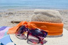 Straw hat, sunglasses and a book on the beach with sea in backgo Royalty Free Stock Images