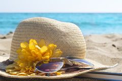 Straw hat, sunglasses and a book on the beach. Summer vacation a Stock Photos