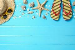 Straw hat, sunglasses, flip flops and many starfishes on color wooden background, space for text and top view. Summer royalty free stock photo