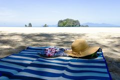 Straw hat, sunglasses and flip flops on a tropical beach. royalty free stock photos