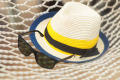 Straw hat and sunglasses on a hammock Royalty Free Stock Image