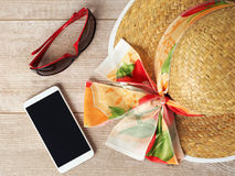 Straw hat, sunglasses and mobile phone stock image
