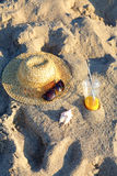 Straw hat, sunglasses, orange juice and seashell on the sand at the beach Stock Photos