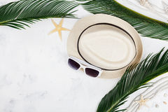 Straw hat, sunglasses, palm leaves, rope, seashell, starfish on table top view, flat lay. Summer holidays, travel,vacation. Royalty Free Stock Photo