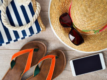 Straw hat, sunglasses, smartphone and slippers stock images